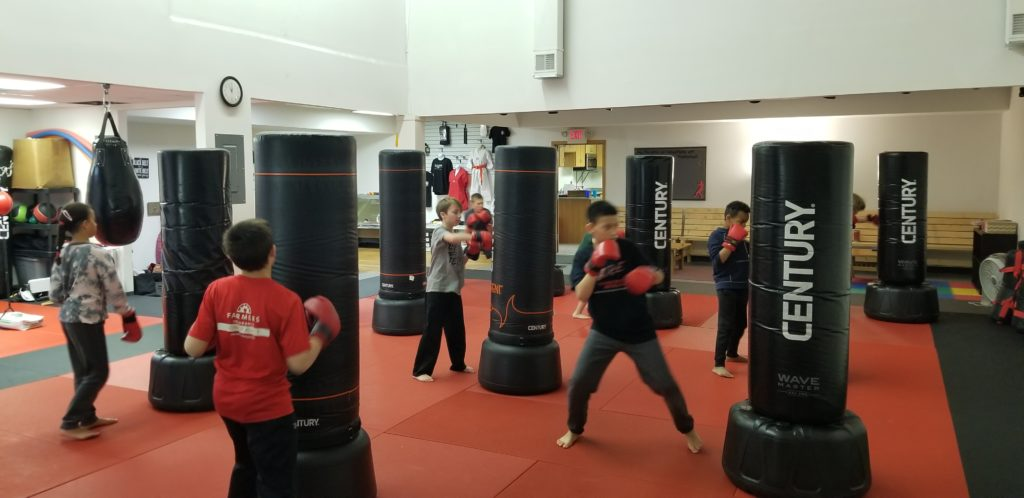 Kids Practicing Boxing on Heavy Bags